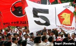 Polisi mengawal pendukung Partai Demokrasi Indonesia Perjuangan (PDI-P) dan Partai Gerakan Indonesia Raya (GERINDRA) di Komisi Pemilihan Umum di Jakarta, 16 Mei 2009. (Foto: REUTERS/Supri)