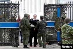 3月19日一名乌克兰海军军官带着私人物品离开位于克里米亚的乌克兰海军司令部
