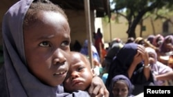 An internally displaced Somali girl carries her sibling as they wait to collect food relief from the World Food Program (WFP) at a settlement in Mogadishu August 7, 2011.