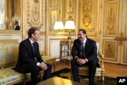 French President Emmanuel Macron, left, confers with Lebanon's Prime Minister Saad Hariri at the Elysee palace in Paris, Saturday, Nov. 18, 2017.