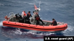 Petugas Garda Pantai AS saat mengevakuasi korban kecelakaan kapal di perairan Key West, Florida 7 Juli 2021. (Foto: U.S. Coast Guard via AP)