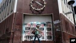 Seorang perempuan berjalan di depan sebuah bank yang ditutup di kawasan Rio Piedras di San Juan, Puerto Rico (foto: ilustrasi). Puerto Rico menghadapi krisis finansial dan harus menutup beberapa bank di sana.
