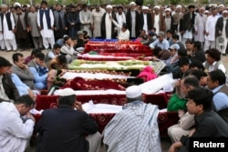 Relatives and others gather at a funeral for the victims of a blast at vegetable market, at a cemetery in Quetta, Pakistan, April 12, 2019.