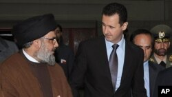 Hezbollah leader sheik Hassan Nasrallah, left, speaks with Syrian President Bashar Assad (AP Photo/SANA, File)