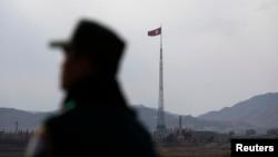 ທຸງ ເກົາຫຼີເໜືອ ປິວສະບັດຢູ່ເທິງປາຍເສົາ ທີ່ບ້ານ ໂຄສະນາ ໃນເມືອງ Gijungdong, ເກົາຫຼີເໜືອ, ເຊິ່ງຮູບນີ້ຖືກ ຖ່າຍຢູ່ໃກ້ກັບບ້ານຢຸດຮົບຊົ່ວຄາວ Panmunjom.