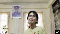 Pro-democracy leader Aung San Suu Kyi pauses during an interview with the Associated Press as a portrait of her father, independence hero Gen. Aung San, hangs on the wall at the National League for Democracy headquarters in Rangoon, Burma, 18, Nov. 2010.
