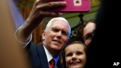 Phó Tổng thống Mike Pence cầm điện thoại của khách chụp ảnh trong khu phức hợp Tòa Bạch Ốc, tháng 5/2017