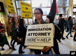 A woman offers legal services at the customs arrival area as demonstrators opposed to President Donald Trump's executive orders barring entry to the U.S. by Muslims from certain countries march behind at the Tom Bradley International Terminal at Los Angel