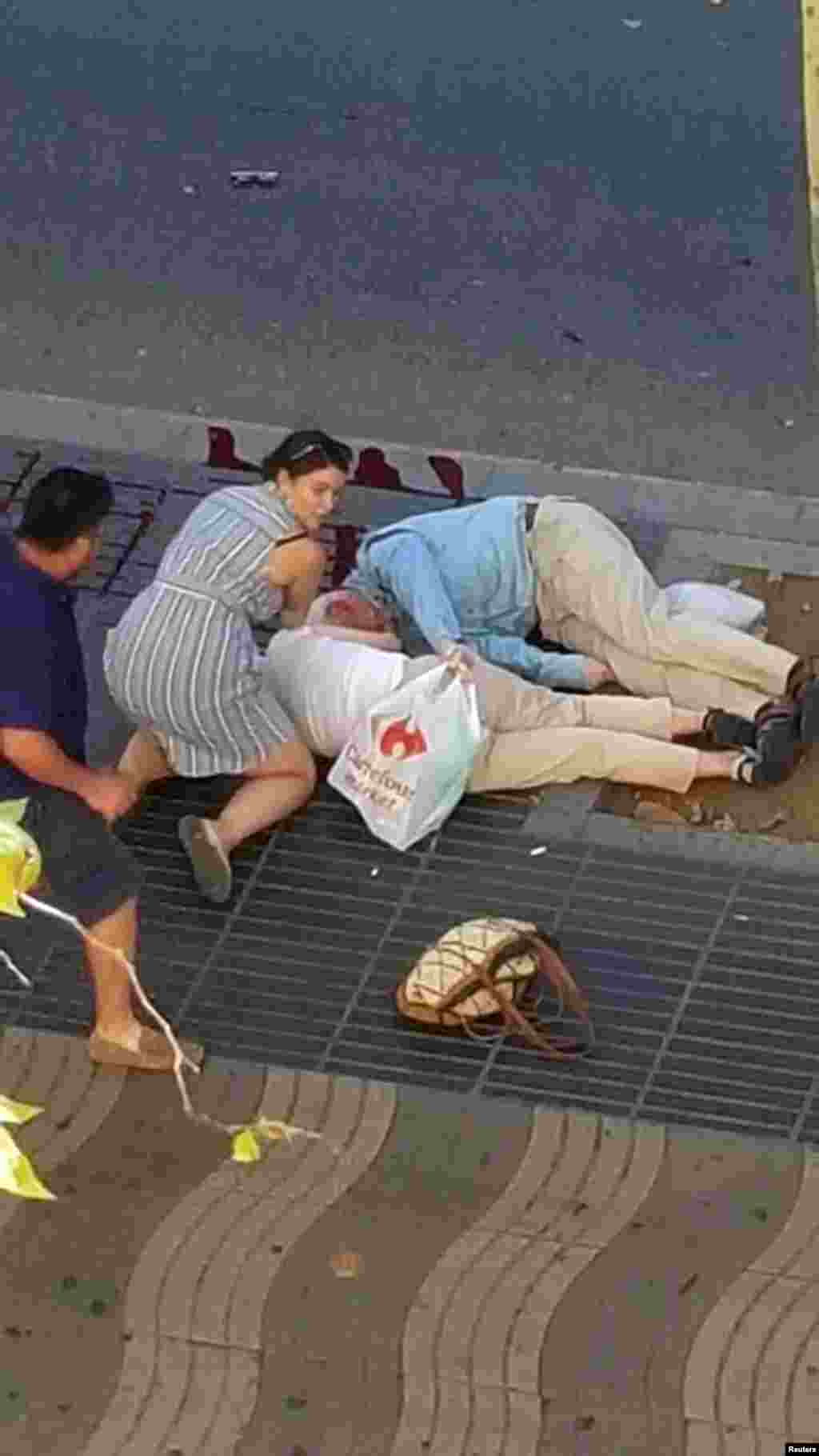 People attend to injured persons at the scene after a van crashed into pedestrians near the Las Ramblas avenue in central Barcelona, Spain, Aug. 17, 2017.