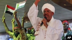 Supporters wave flags as Sudanese President Omar al-Bashir addresses a rally in Khartoum, Sudan, April 18, 2012.