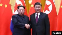 中共中央总书记、国家主席习近平和朝鲜劳动党委员长、国务委员会委员长金正恩在北京人民大会堂握手(2018年3月28日发布的照片)