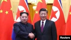 習近平和金正恩在北京人民大會堂握手。(2018年3月28日的照片)
