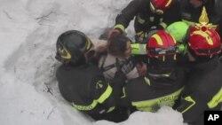 Para petugas menyelamatkan seorang perempuan dari longsoran salju di Rigopiano, Italia Januari tahun lalu (foto: ilustrasi).