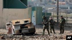 Soldados del Ejército iraquí inspeccionan un coche bomba que estalló en un barrio recientemente liberado de militantes islámicos en el lado oriental de Mosul, Irak, este domingo 8 de enero de 2017.