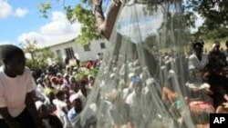 Oxfam workers demonstrate how to erect mosquito nets in the Gutu district of Zimbabwe, about 290km southeast of Harare (File Photo)