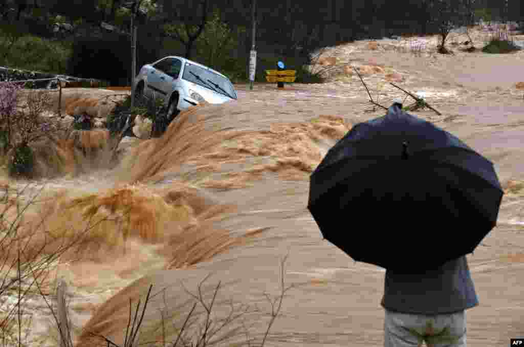 Flash floods caused by torrential rain go down a street on the outskirts of Jerusalem, Israel.