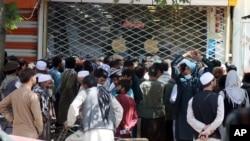 喀布尔银行前,一群阿富汗人等待数小时,试图取钱。
