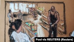 A store surveillance video of Floyd counting money plays on a screen as Cup Foods
