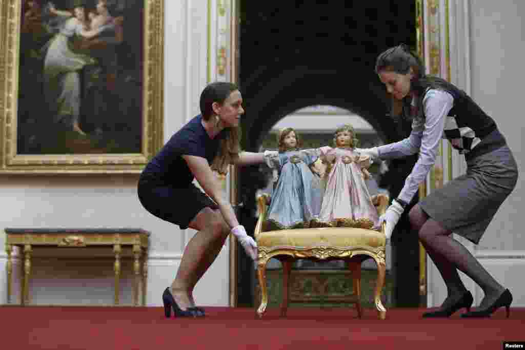 "Exhibition curator Anna Reynolds (L) poses with a pair of Parisian dolls belonging to Britain's Queen Elizabeth (left doll) and her sister Princess Margaret, at Buckingham Palace in London. Toys and childhood outfits belonging to the royal family will form part of an exhibition ""Royal Childhood"" during the summer opening of Buckingham Palace from Jul. 26 - Sept. 28, 2014."