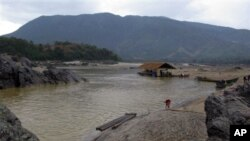 A woman works on the bank of the Irrawaddy river in Kachin State, northern Burma.