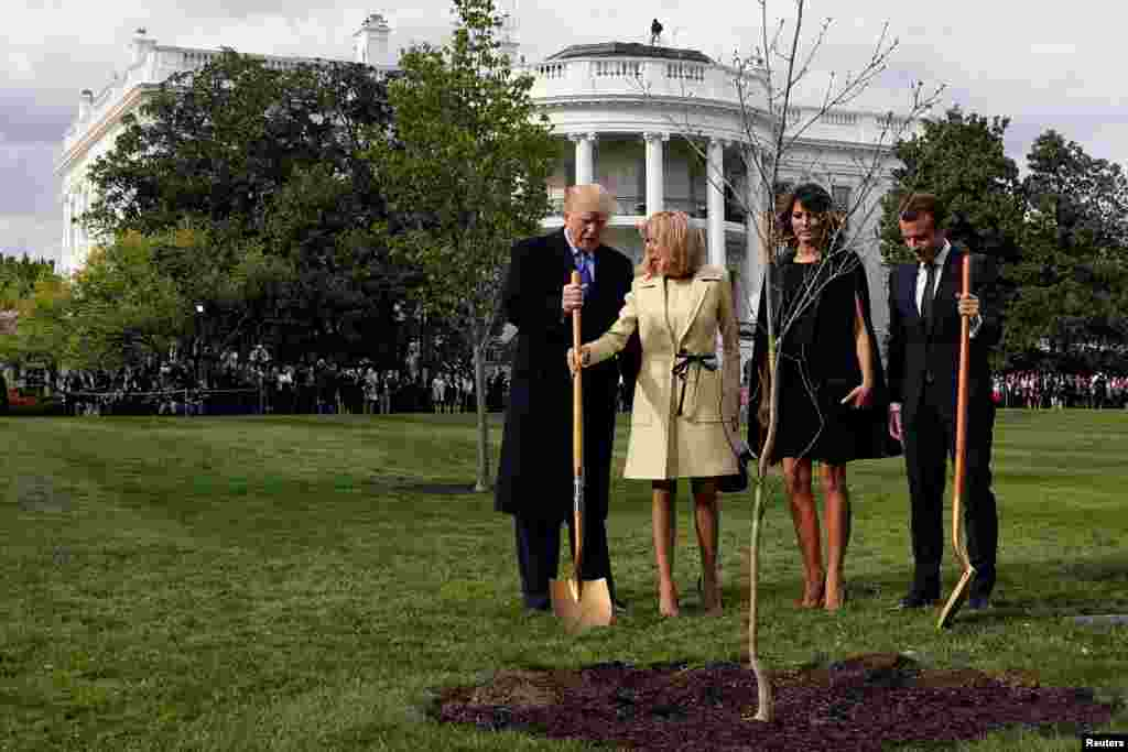 Brigitte Macron holds the shovel used by U.S. President Donald Trump after a tree planting as and first lady Melania Trump and French President Emmanuel Macron stand on the South Lawn of the White House in Washington, April 23, 2018.
