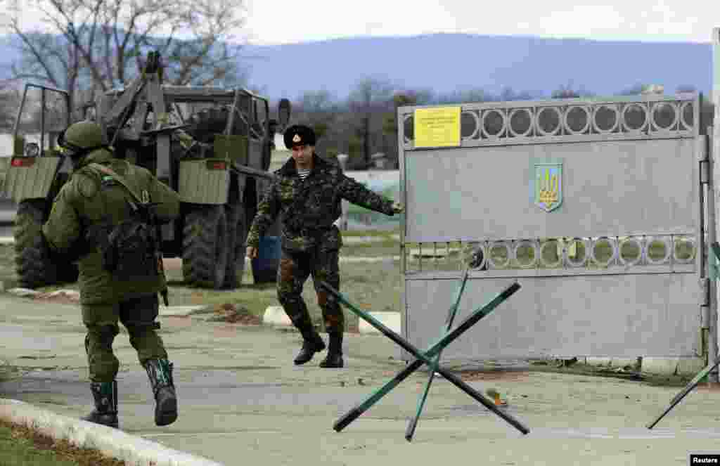 A Ukrainian serviceman closes a gate as an armed man, believed to be a Russian serviceman, stands guard outside an Ukrainian military base in Perevalnoye, near the Crimean city of Simferopol March 13, 2014.