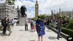ຜູ້ປະທ້ວງຄົນໜຶ່ງ ທີ່ປົກຄຸມດ້ວຍທຸງຂອງສະຫະພາບຢູໂຣບ ຫຼື EU ເຂົ້າຮ່ວມໃນການປະທ້ວງຄັດຄ້ານ ການຖອນຕົວ ອອກ ຈາກ EU ຢູ່ທີ່ຈະຕຸລັດ ສະພາ ຫຼັງຈາກຜົນການລົງ ປະຊາມະຕິ ໄດ້ປະກາດອອກມາ, ນະຄອນລອນດອນ, ວັນທີ 25 ມິຖຸນາ 2016.