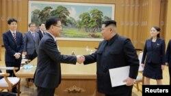 朝鲜领导人金正恩在平壤与来访的韩国最高安全顾问郑义溶握手(2018年3月6日)