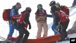United States' Arielle Gold is assisted after injuring her hand after falling during the women's snowboard halfpipe warm-up, Feb. 12, 2014, in Krasnaya Polyana, Russia.