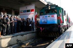 FILE - Iranian officials applaud on the platform as the first train connecting China and Iran arrives at Tehran Railway Station, Feb. 15, 2016.