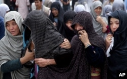 FILE - Afghan women mourn during the funeral of victims who died from a suicide attack, in Kabul, Afghanistan, July 24, 2016.