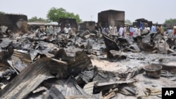 FILE - People stand outside burned houses following an attack by Islamic militants in Gambaru, a city in Nigeria's Borno state, May 11, 2014.