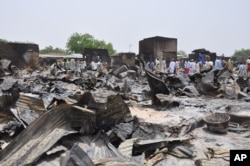 FILE - People stand outside burned houses following an attack by militants in Gambaru, a city in Nigeria's Borno state, May 11, 2014.