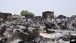 Orang-orang berdiri di luar rumah-rumah yang terbakar setelah terjadi serangan kelompok militan Boko Haram di Gambaru, Borno, Nigeria, 11/5/2014.