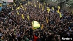 Anggota kelompok Hizbullah mengangkat peti mati yang membawa jenazah komandan militer mereka, Mustafa Badreddine, ke tempat pemakaman di kawasan sub-urban selatan Beirut, Lebanon (13/5).