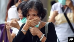A relative of a victim of AirAsia Flight 8501 waits for the handover of the body to the family at a police hospital in Surabaya, East Java, Indonesia, Monday, Jan. 5, 2015.