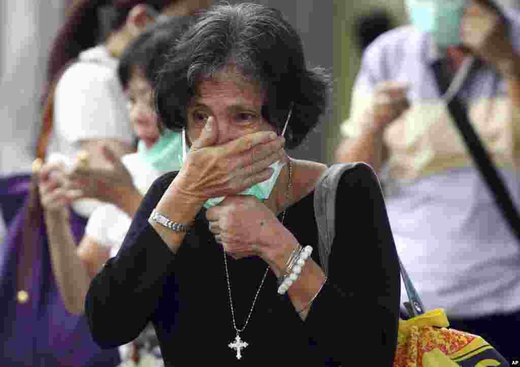 Seorang kerabat korban jatuhnya pesawat AirAsia bernomor penerbangan 8501 menangis saat menunggu serah terima jenazah di rumah sakit polisi di Surabaya (5/1). (AP/Firdia Lisnawati)