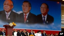 From left to right seated in front row, Cambodian National Assembly President Heng Samrin, Senate President Chea Sim, Prime Minister Hun Sen, and his wife Bun Rany attend an event by the ruling Cambodian People's Party marking the 35th anniversary of the 1979 downfall of the Khmer Rouge regime at Koh Pich, in Phnom Penh, Cambodia, Tuesday, Jan. 7, 2014.