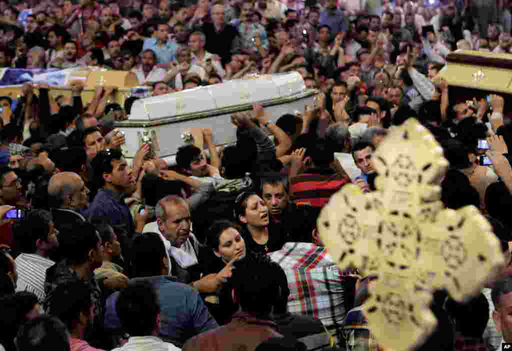 Egyptian Christians carry four coffins during a funeral service, at the Saint Mark Coptic cathedral in Cairo, Egypt, April 7, 2013.