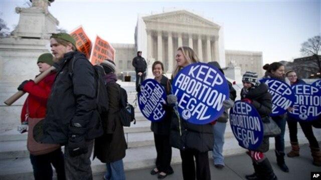 Bettina Hager (tengah) dan Jeff Foster (kiri) bergabung dalam peringatan 40 tahun Roe versus Wade, keputusan  MA yang melegalkan aborsi di Amerika, di depan Mahkamah Agung AS di Washington DC, Selasa 22 Januari 2013. (APhoto/Manuel Balce Ceneta)