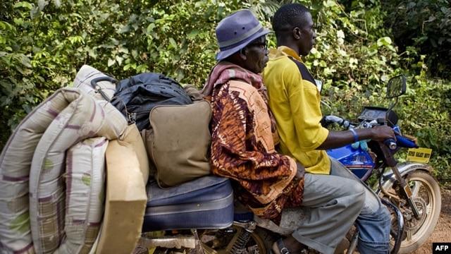 FILE - An Ivorian refugee gets a lift on motor bike taxi toward Zwedru, Liberia, March 24, 2011.