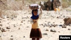 Une petite fille porte de l'eau dans un camp de réfugiés entre Marib et Sanaa, Yémen, le 29 mars 2018