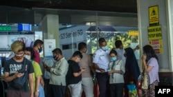 Para pengunjung sebuah mal di Suranaya, memindai kode QR untuk menunjukkan pelacakan kontak tentang keberadaan mereka di tengah perpanjangan PPKM, 10 Agustus 2021. (Foto: Juni Kriswanto/AFP)