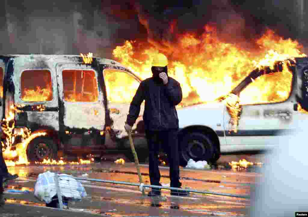 A demonstrator stands in front of burning vehicles during fighting between riot police and demonstrators in central Brussels, Belgium.