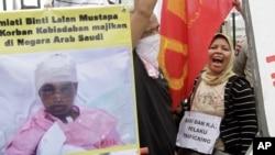 Para tenaga kerja Indonesia meneriakkan slogan-slogan dalam demonstrasi di luar gedung DPR/MPR, memprotes penyiksaan seorang tenaga kerja Indonesia di Arab Saudi, Jakarta, 23 November 2010.