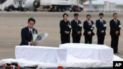 日本外相岸田文雄(左)在东京羽田机场向遇难者的灵柩献花(2016年7月5日)