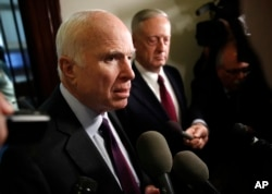 FILE - Sen. John McCain, R-Ariz., left, and Defense Secretary James Mattis speak to reporters after their meeting on Capitol Hill in Washington, Oct. 20, 2017.