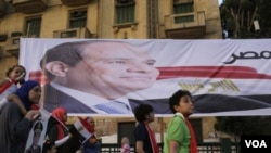 Warga Mesir berjalan melewati poster mantan pemimpin militer Abdel Fattah al-Sisi di Lapangan Tahrir dan merayakan kemenangannya dalam Pemilu Presiden di Kairo (3/6).