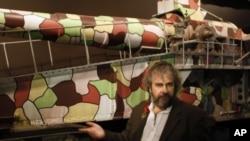 Sutradara Peter Jackson berdiri di depan meriam aneka warna dari masa Perang Dunia I pada pameran museum yang ia selenggarakan di Wellington, Selandia Baru, 2015.