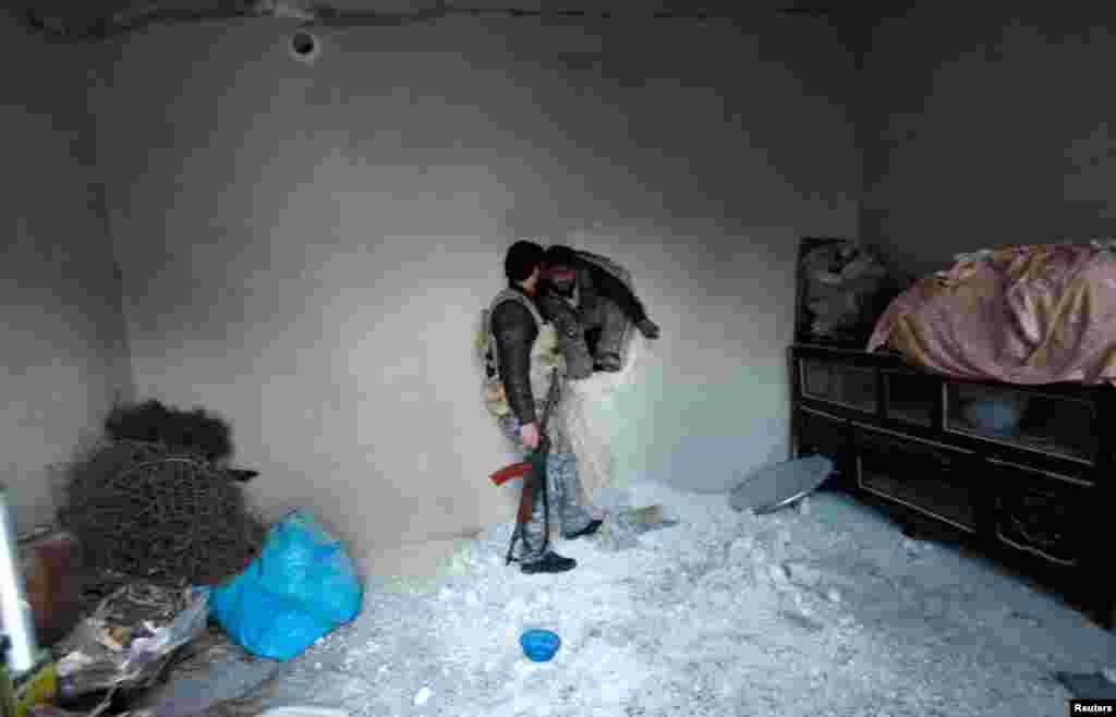 17일 알레포 공항 인근에서 무너진 아파트 내부를 지나는 반군.